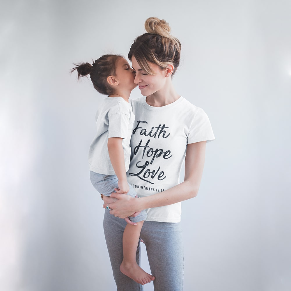 Woman Wearing A Christian Faith Hope Love White T Shirt Being Kissed By Her Daughter